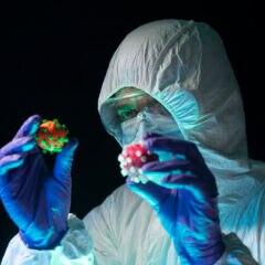 Ein Wissenschaftler im Schutzanzug hält symbolhafte Coronaviren in den Händen