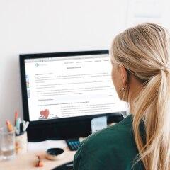 Eine Frau liest etwas auf dem PC