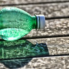 Angebrochene Wasserflasche liegt auf Holzboden