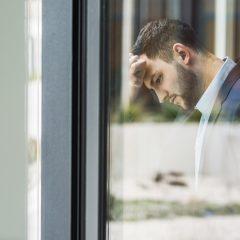 Ein Mann im Business-Outfit lehnt erschöpft an einem Fenster